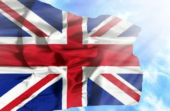 Great Britain waving flag against blue sky with sunrays vector illustration