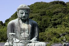 Great Buddha of Kamakura Japan. Great Buddha of Kamakura in a Jappanese Temple against a blue sky and green hill top royalty free stock photography
