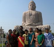 Great Buddha Statue Indian Family Caucasian Woman. An Indian Family with visiting Caucasian woman pose in front of The Great Buddha Statue in Bodhgaya, India. It stock image