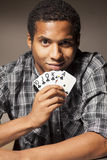 Great card combination. Affrican man holding a winning combination of poker cards Stock Photography