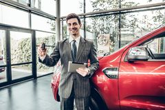Great choise! Handsome young classic car salesman standing at the dealership holding a key. Handsome young classic car salesman standing at the dealership royalty free stock image