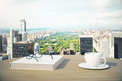 Great city view with cup of coffee, book and glasses Stock Images