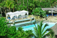 Great comfortable white gazebos near the pool in tropical palm trees garden Stock Photography