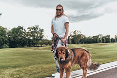 Great companion. Full length of handsome young man standing with his dog while spending time outdoors Stock Photos