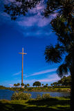 Great Cross St Augustine Florida. Low angle view of Great Cross with blue sky and cloudscape framed by trees royalty free stock photos