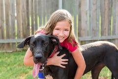 Great dane e jogo do abraço da menina da criança exterior Fotos de Stock Royalty Free