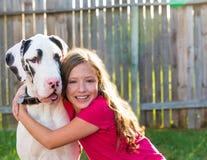 Great dane e jogo do abraço da menina da criança exterior Imagens de Stock Royalty Free