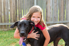 Great dane and kid girl hug playing outdoor Royalty Free Stock Photos