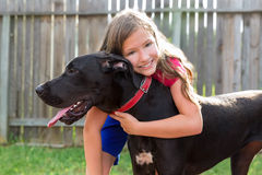 Great dane and kid girl hug playing outdoor Stock Image