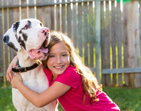 Great dane and kid girl hug playing outdoor Stock Photo
