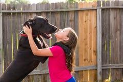 Great dane levanta-se no jogo dos ombros da menina da criança Fotografia de Stock