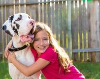 Great dane y el jugar del abrazo de la muchacha del niño al aire libre Foto de archivo