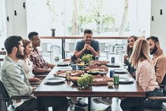 Great day with friends. Group of young people in casual wear talking and smiling while having a dinner party in the restaurant stock images