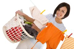 Great day for laundry. Young smiling woman hanging clothes on clothesline using clothespin. She holding clothes hamper in hands. Front view, looking at camera stock photos