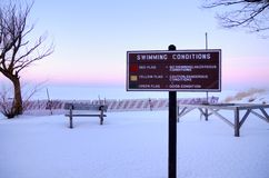 Great Day For A Swim. Great Lakes coast encased in snow and ice complete with a sign updating the current swimming conditions.   Port Crescent State Park.  Port Royalty Free Stock Photos