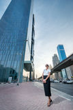 Great deals. Successful arabic businesswoman standing. In the street in formal attire. Businessman standing near skyscrapers in Dubai downtown in sunglasses Royalty Free Stock Photography