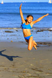 Young girl jumping at the beach. A young girl jumps on summer day. Great escape to the beach Royalty Free Stock Image