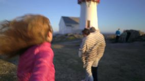 Young Woman with her big family Leading her husband walking towards rocky northern beach. A great family adventure. Follow me. Young Woman with her big family stock video footage