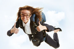 Great flight. Conceptual image of young female flying with parachute and showing thumbs up Stock Photo