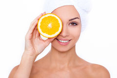 Great food for a healthy lifestyle. Beautiful young shirtless woman holding piece of orange in front of her eye while standing against white isolated background Royalty Free Stock Images