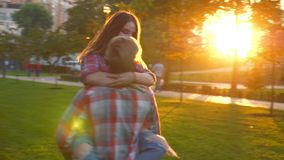 Great footage of love, boy is kissing his girlfriend and holding her with hands, turning on circle and moving in green. Park, fresh illustration, modern people stock video footage