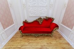 Great  fragment of view of luxury interior guest room with old vintage retro, bright red couch, sofa on hardwood floor Stock Photo