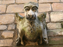 Great Gargoyles. A hideous gargoyle stares down from an old roof in York, England stock photography