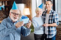 Cheerful elderly man showing present for his son. Great gift. Upbeat senior men in a party hat showing a box with a present for his adult son while he hugging Stock Photos
