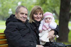 Great-grandfather, grandmother and little baby girl on a bench in the park Royalty Free Stock Photos