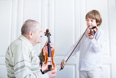 Great grandfather listening to a child playing violin. On white room Stock Photo
