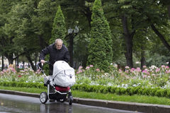 Great-grandfather walking with a stroller on a cold rainy day in a beautiful park. Happy great-grandfather walking with a stroller on a cold rainy day in a Royalty Free Stock Photography