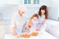 Great grandmother baking apple pie with her family. Great grandmother baking an apple pie with her family, young granddaughter and a cute curly toddler girl in a Stock Photos