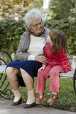 Great grandmother and child. Sitting on a bench in the park and looking at each other Stock Photography