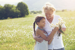 Great-grandmother and granddaughter. Standing in flower field in sunlight Royalty Free Stock Photo