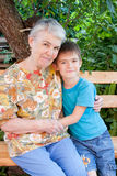 Great-grandmother and great-grandchild. Cheerful great-grandmother and great-grandchild in a garden Stock Photo