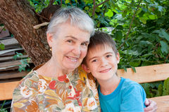 Great-grandmother and great-grandchild. Cheerful great-grandmother and great-grandchild in a garden Stock Photography