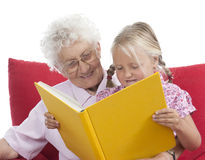 Great-grandmother and great-granddaughter. Great grandmother and great granddaughter reading a book together Royalty Free Stock Photography