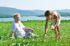 Great grandmother and great granddaughter in meadow Royalty Free Stock Image