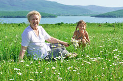Great grandmother and great granddaughter in meadow Stock Image