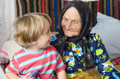 Great Grandmother and her Great Grandson. In a rustic home Stock Image