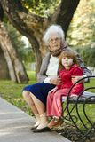 Great grandmother and kid. Sitting on the bench in the park looking away together Royalty Free Stock Photos