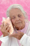 Great Grandmother Listening. Smiling great grandmother listening to a seashell. Pink background. Woman in her eighties Stock Images
