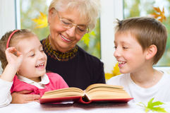 Great-grandmother reading a book for grandchildren. At home Royalty Free Stock Image