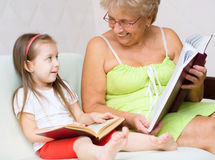 Great-grandmother reading a book. Great-grandmother with her granddaughter are reading a book at home Royalty Free Stock Photos