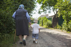 Great grandmother and toddler boy holding hands while walking down street Royalty Free Stock Photo