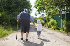 Great grandmother and toddler boy holding hands while walking down street. Stock Photo