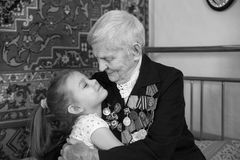 Great-grandmother - a veteran of World War II, and her great-granddaughter. Of a black and white photo Royalty Free Stock Photo
