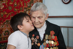 Great-grandmother - a veteran of World War II, and her great-grandson. A kiss on the cheek Stock Photo