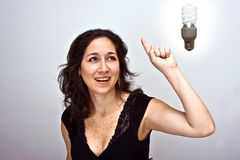 Great idea!. Woman having a brilliant environmentally friendly idea and a compact fluorescent light bulb above her head stock photo