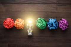 Great idea concept. With crumpled colorful paper and light bulb on wooden table stock images